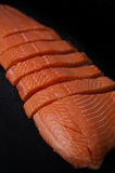 Fresh salmon pieces on dark black background royalty free stock images