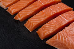 Fresh salmon pieces on dark black background stock photography