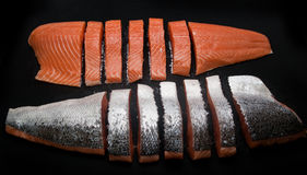 Fresh salmon pieces on dark black background royalty free stock photography