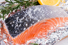 Fresh salmon ready for cooking on the foil paper. Royalty Free Stock Images
