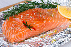 Fresh salmon ready for cooking on the foil paper. Stock Images