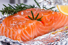 Fresh salmon ready for cooking on the foil paper. Fresh salmon ready for cooking on the foil paper Stock Image