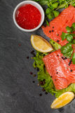 Fresh salmon and red caviar on black plate Royalty Free Stock Photos