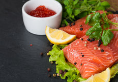 Fresh salmon and red caviar on black plate Stock Image