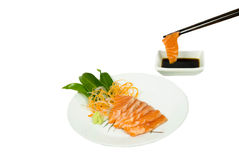 Fresh salmon sashimi with chopsticks and sauce isolated Royalty Free Stock Images