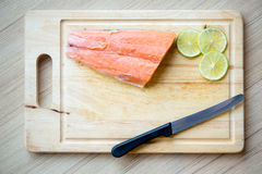 Fresh salmon with skin, lemon slice, fork ,tongs and knife on wood chopping board. Image for background, wallpaper and copy space. fresh ingredient for clean Royalty Free Stock Photo