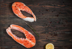 Fresh salmon slice with spice on old wood background.  Royalty Free Stock Images
