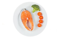 Fresh salmon steak. A fresh salmon steak with broccoli and cherry tomatoes on a white plate. Shallow depth of field Stock Photo