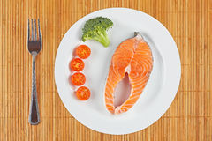 Fresh salmon steak. A fresh salmon steak with broccoli and cherry tomatoes on a white plate. Shallow depth of field Royalty Free Stock Photography