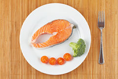 Fresh salmon steak. A fresh salmon steak with broccoli and cherry tomatoes on a white plate. Shallow depth of field Royalty Free Stock Image