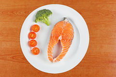 Fresh salmon steak. A fresh salmon steak with broccoli and cherry tomatoes on a white plate. Shallow depth of field Royalty Free Stock Photos