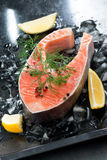 Fresh salmon steak with dill and lemon on ice, vertical. Top view Stock Image