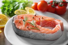 Fresh salmon steak with herbs. On white plate Royalty Free Stock Photography