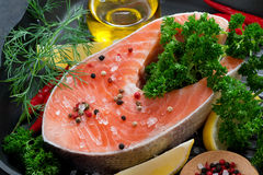 Fresh salmon steak and ingredients for cooking on a grill pan Royalty Free Stock Image