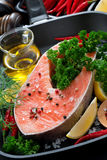 Fresh salmon steak and ingredients for cooking on a grill pan Stock Photography