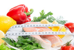 Fresh salmon steak for lunch with tape measure and salad tomatoe Royalty Free Stock Images