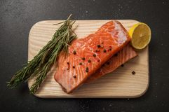 Fresh salmon steak surrounded by lemon, spices and herbs on a wooden board. Black background.