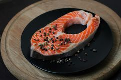 Fresh salmon steaks being marinated in pot Royalty Free Stock Images