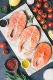 Fresh salmon steaks, herbs, olive oil and cooking ingredients on marble background stock images