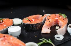 Raw salmon steaks on the dark stone background. Fresh salmon steaks with ingredients for cooking board, top view Royalty Free Stock Photography