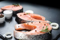 Raw salmon steaks on the dark stone background. Fresh salmon steaks with ingredients for cooking Stock Image