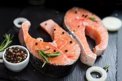 Raw salmon steaks on the dark stone background. Fresh salmon steaks with ingredients for cooking Royalty Free Stock Images