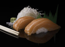 Fresh salmon sushi close up served on a black reflective surface. Two pieces of Japanese salmon sushi on a black reflective surface served with wasabi and white royalty free stock photos