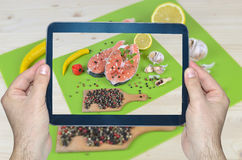 Fresh Salmon on Tablet. Man hands with tablet taking photo of colorful food - salmon steaks surrounded with spices - ready for cooking Stock Photos