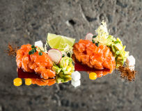 Fresh salmon tartar. With garnish over concrete background Stock Photos