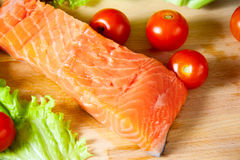 Fresh salmon with tomatoes on a cutting board. Selective focus. Fresh salmon with fresh tomatoes on a cutting board. Selective focus Stock Photos
