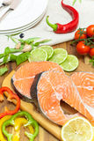 Fresh salmon, vegetables and herbs. Marinated salmon steaks prepared for frying on grill pan Royalty Free Stock Photos