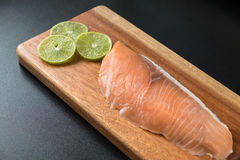 Fresh salmon on wooden tray. Selective focus on fresh salmon on wooden tray with sliced green lemon Stock Image