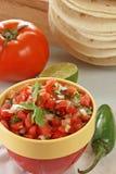 Fresh salsa. Bowl of fresh tomato salsa with whole jalapeno, tomato, lime, and flour tortillas