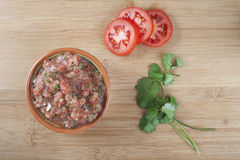 Fresh Salsa. Bowl of fresh salsa with tomato slices and cilantro viewed from directly above stock images