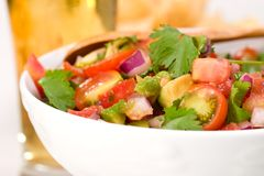 Fresh salsa. Closeup of a bowl with fresh cherry tomatoes and avocado salsa. Glass of beer out of focus stock photo