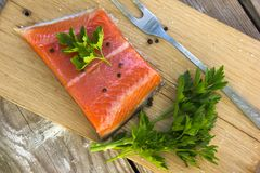 Fresh salted salmon fillet with herbs spice on a wooden board. C. Oncept of healthy food Stock Photography
