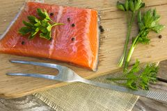 Fresh salted salmon fillet with herbs spice on a wooden board. C. Oncept of healthy food Stock Photos