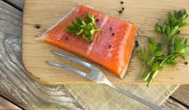 Fresh salted salmon fillet with herbs spice on a wooden board. C. Oncept of healthy food Stock Image