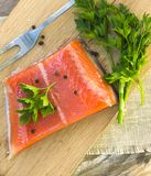 Fresh salted salmon fillet with herbs spice on a wooden board. C Stock Photos