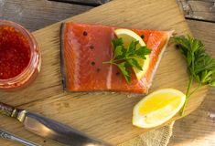 Fresh salted salmon fillet with herbs spice on a wooden board. C Stock Photography