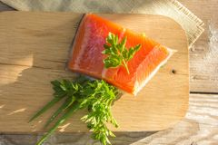 Fresh salted salmon fillet with parsley and onion on a wooden bo. Ard. Concept of healthy food Royalty Free Stock Image