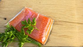 Fresh salted salmon fillet with parsley and onion on a wooden bo. Ard. Concept of healthy food Royalty Free Stock Photo