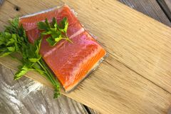 Fresh salted salmon fillet with parsley and onion on a wooden bo. Ard. Concept of healthy food Stock Images