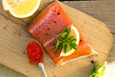 Fresh salted salmon fillet with red caviar, herbs, spice on a wo. Oden board. Concept of healthy food Royalty Free Stock Photos