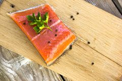 Fresh salted salmon fillet with parsley and onion on a wooden bo. Fresh salted salmon fillet spice on a wooden board. Concept of healthy food Royalty Free Stock Image