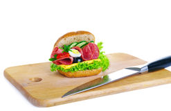 Fresh sandwich and a knife lying on a wooden board Stock Image