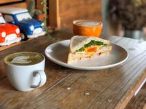 Fresh sandwich in the white dish on the wooden table with natural light, Delicious breakfast. royalty free stock photos
