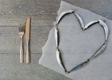 Fresh sardine in heart form and cutlery Royalty Free Stock Photo