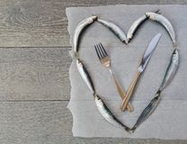 Fresh sardine in heart form and cutlery Stock Image