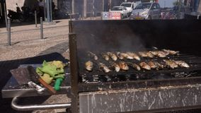 Fresh sardines cooking over a hot barbecue in an open air cafe in Portugal stock video footage